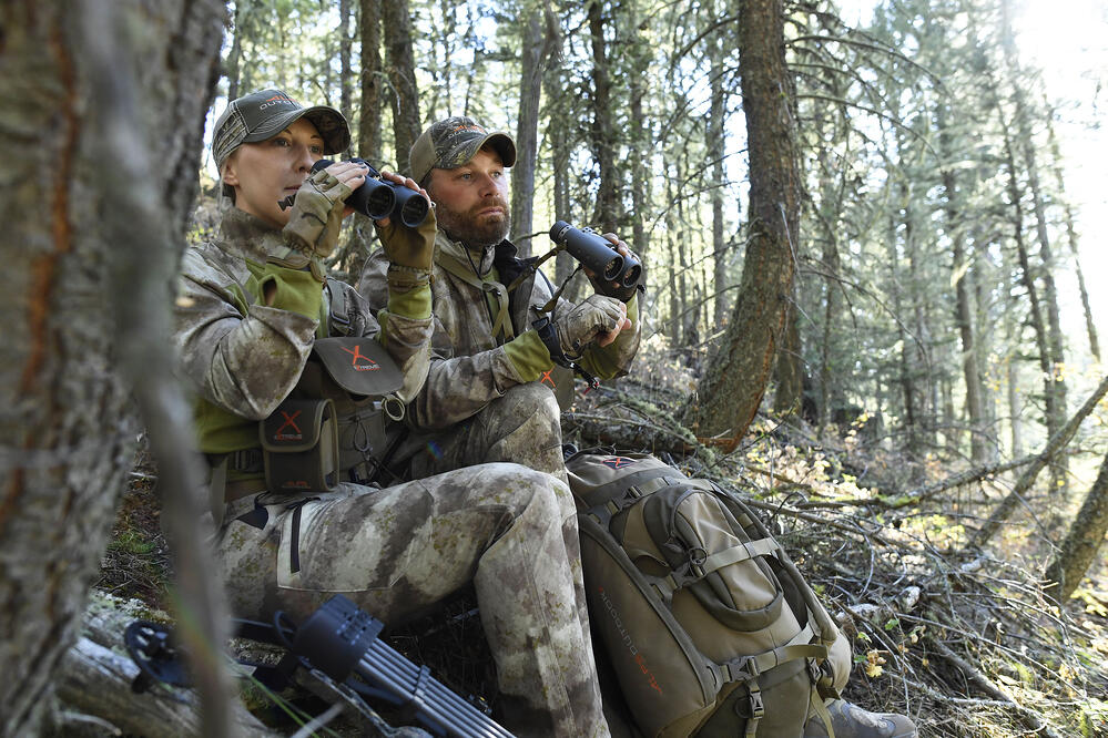 Hunting mentor and mentee scouting for elk in the forest